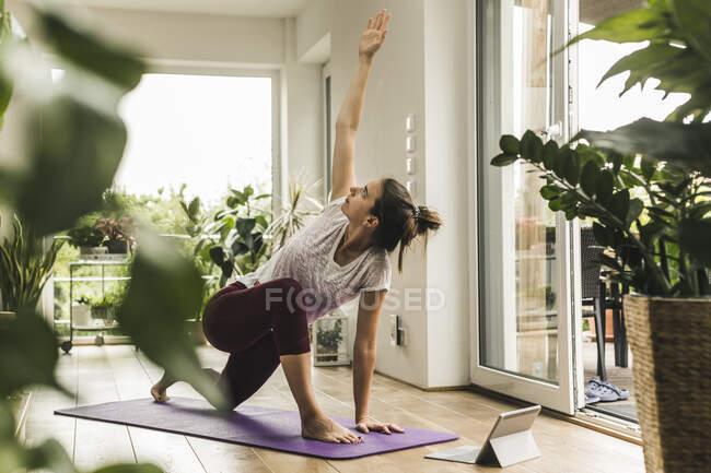 Молодая женщина с цифровым планшетом упражнения на мат дома — стоковое фото
