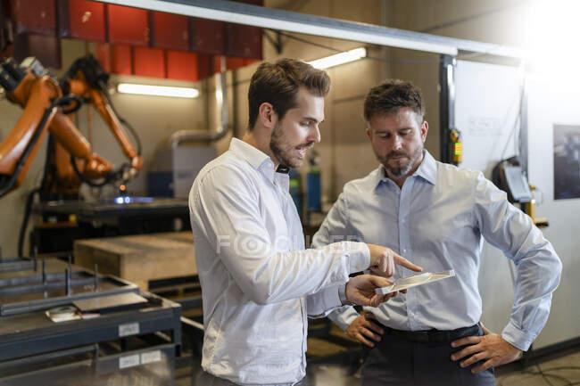 Бізнесмен оглядає металевий предмет стоячи на заводі. — стокове фото