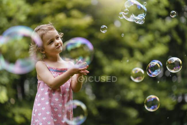 Menina bonito olhando para bolhas enquanto de pé no parque — Fotografia de Stock