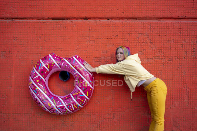 Young woman with dyed hair and floating tyre hanging on red wall - foto de stock