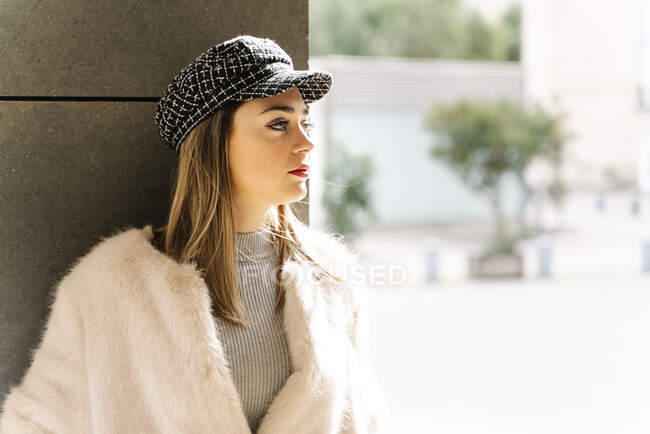 Beautiful woman in jacket looking away against wall — Stock Photo