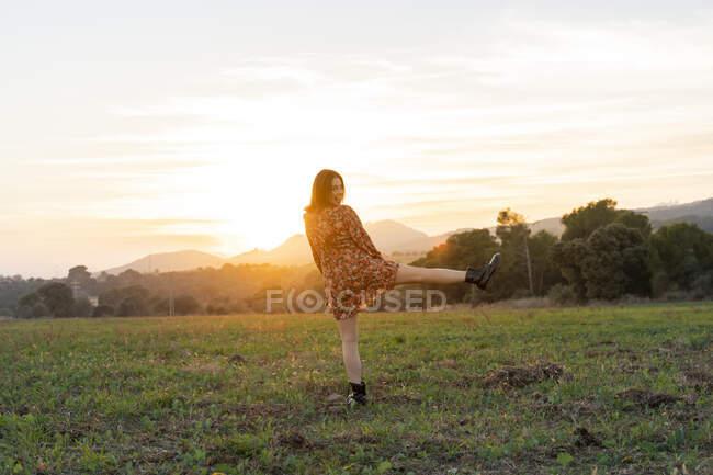Giovane donna allegra in piedi su una gamba a prato durante il tramonto — Foto stock