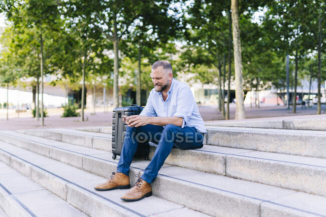 Businessman using mobile phone while sitting by suitcase on steps — Stock Photo