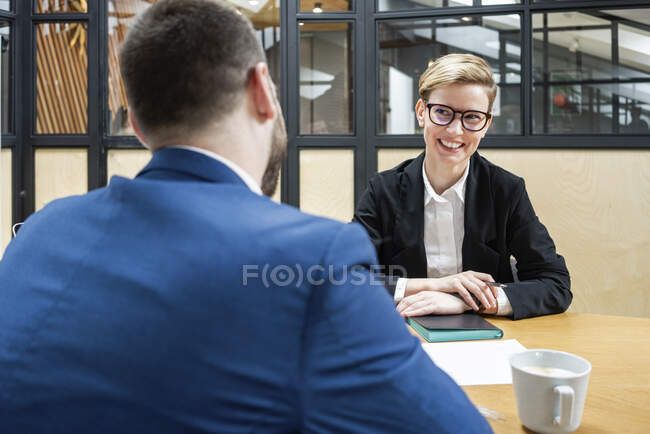 Smiling businesswoman looking at male executive sitting in board room during job interview — Stock Photo