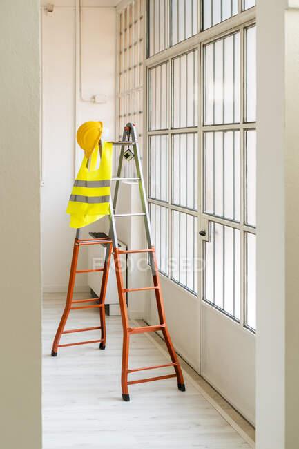 Капелюх і дзеркальний жилет висять на драбині в порожній студії — стокове фото