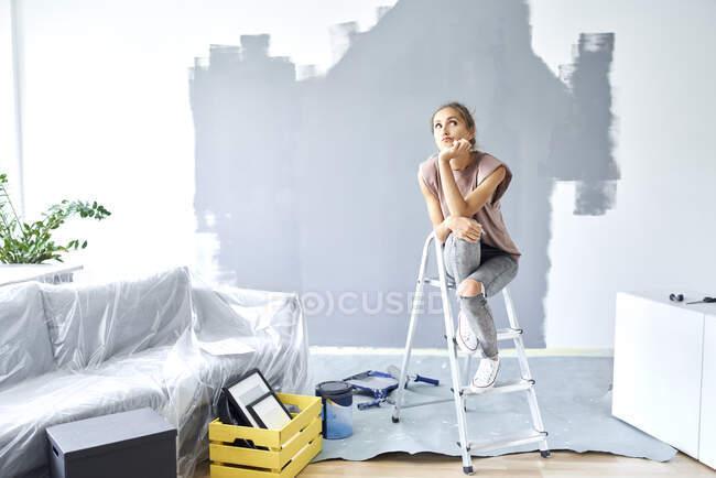 Духовна жінка з головою в руках сидить на драбині біля стіни вдома. — стокове фото