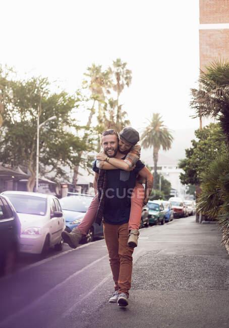 Взрослый мужчина, катающийся на спине для женщины на улице в городе — стоковое фото
