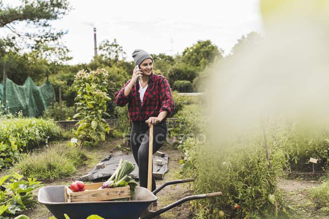 Молода жінка розмовляє по мобільному телефону стоячи на тачці в городі овочів. — стокове фото
