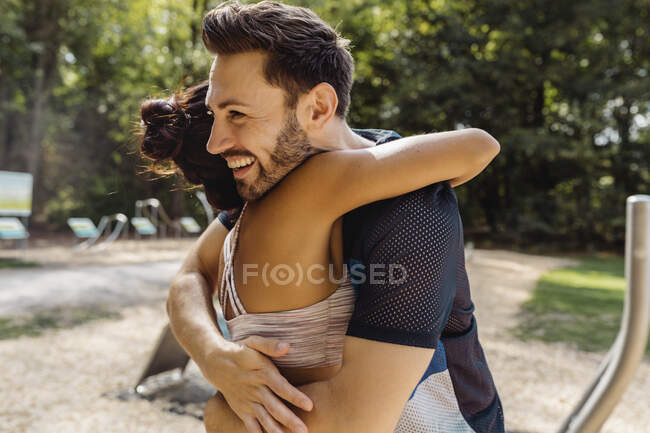 Man and woman hugging on a fitness trail — Stock Photo