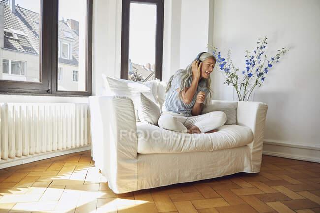 Donna felice che ascolta musica sul divano di casa — Foto stock