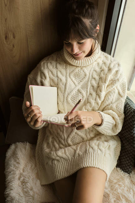 Smiling woman wearing sweater writing in book while sitting by window at home — Fotografia de Stock