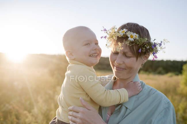 Женщина, носящая венок и несущая веселого сына в солнечный день — стоковое фото