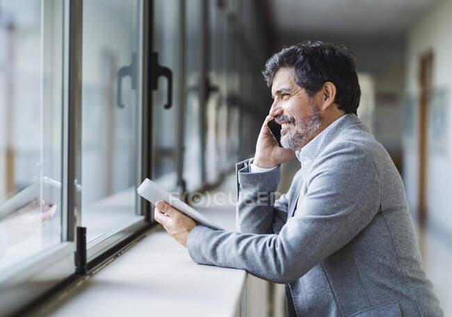 Усміхаючись, професор говорить по телефону, дивлячись через вікно в коридорі в університеті — стокове фото