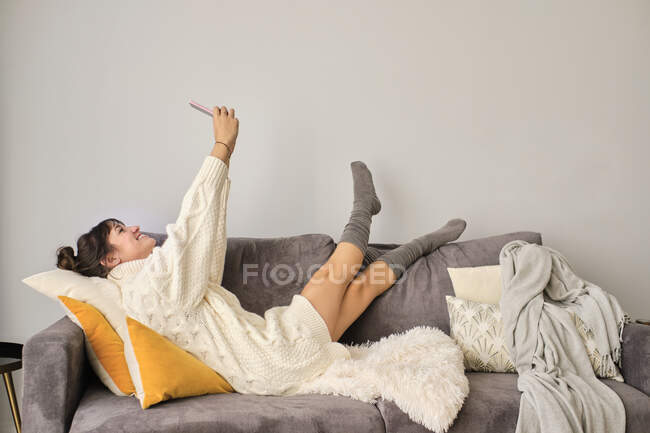 Smiling woman taking selfie through smart phone while relaxing on sofa at home during winter — стокове фото