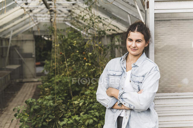 Confident young woman with arms crossed standing by greenhouse — Stock Photo