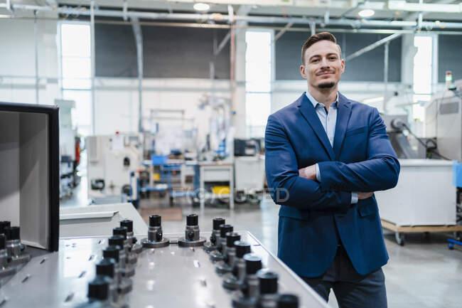 Посмішка бізнесмена з озброєнням, схрещений виробничим обладнанням на заводі — стокове фото