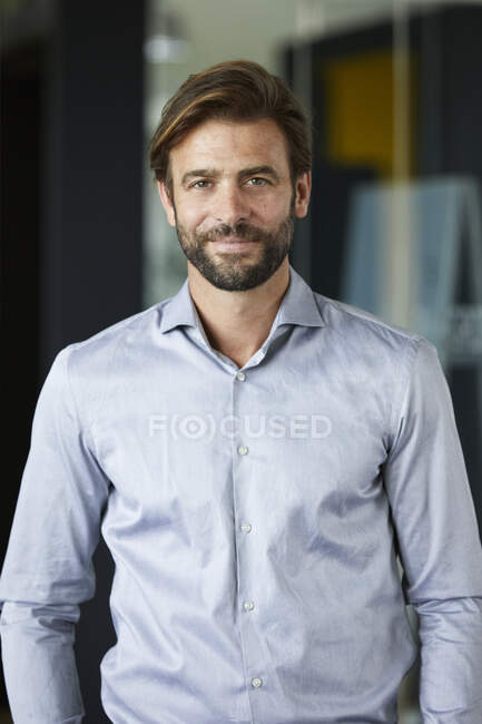 Hombre de negocios sonriente de pie en el cargo - foto de stock