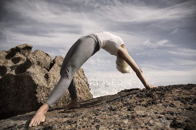 Гибкая женщина практикующая йогу на скалах на пляже — стоковое фото