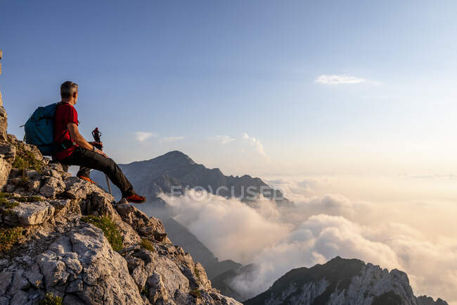 Hiker admiring view while sitting on top of mountain peak at Bergamasque Alps, Italy — Stock Photo