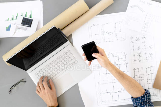 Architect using mobile phone while sitting by desk at office — Stock Photo