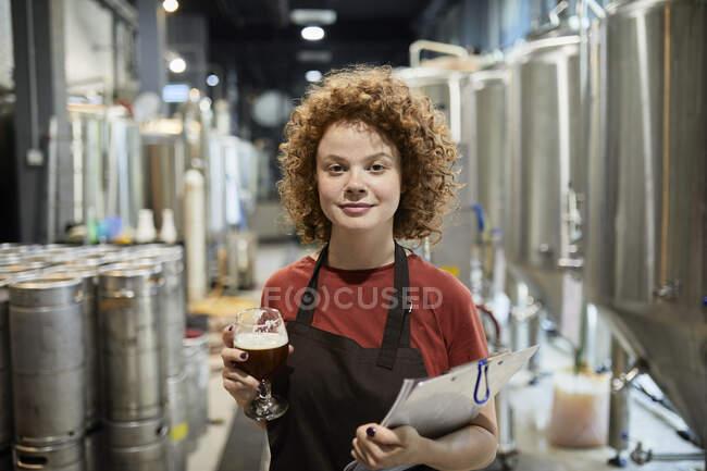Портрет уверенной женщины с планшетом и пивным стеклом в пивоварне — стоковое фото