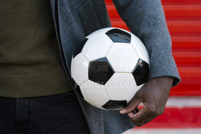 Чоловік тримає футбол, стоячи надворі. — стокове фото