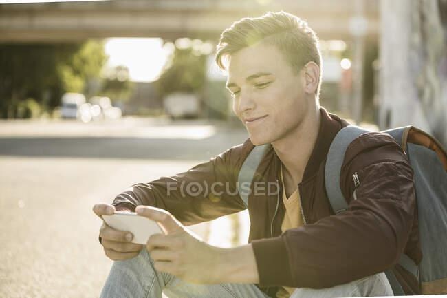 Sonriente hombre guapo usando el teléfono inteligente mientras está sentado en la calle durante el día soleado - foto de stock
