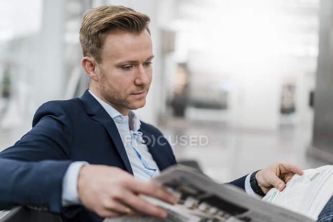 Довірливий бізнесмен, який читає газети, сидячи в місті. — стокове фото