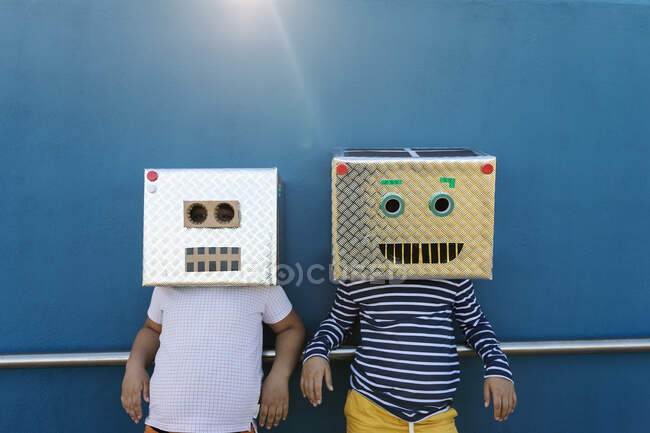 Friends wearing robot costumes made of boxes while standing against blue wall — стокове фото