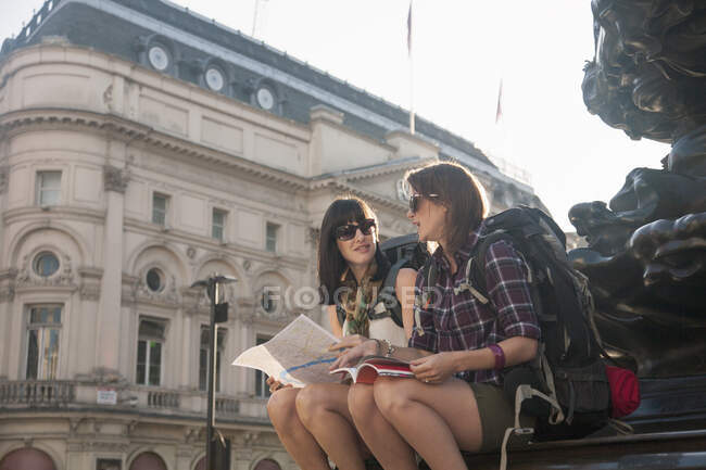 Mochileras discutiendo sobre el mapa mientras están sentadas en la plaza de la ciudad - foto de stock