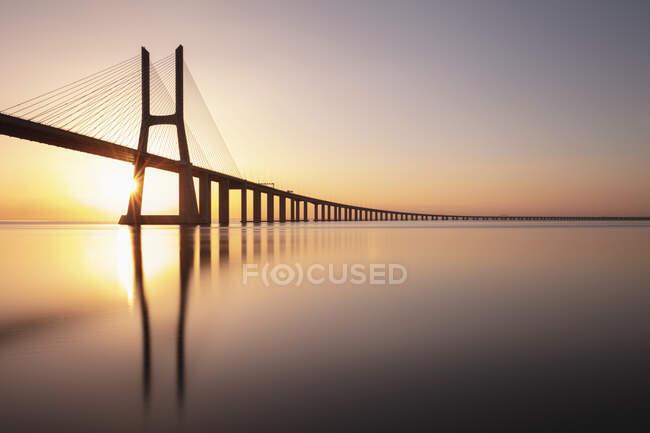 Portugal, Distrito de Lisboa, Lisboa, Puente Vasco da Gama al atardecer - foto de stock