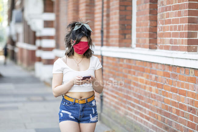 Young woman's face covered with mask using smart phone while standing in city — Stock Photo