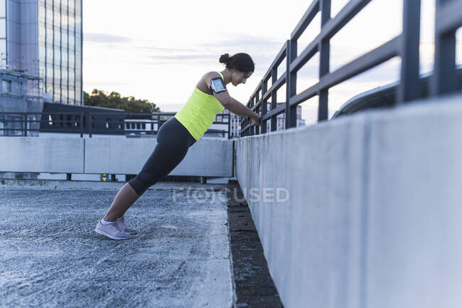 Young woman with arm band exercising on railing at sunset - foto de stock