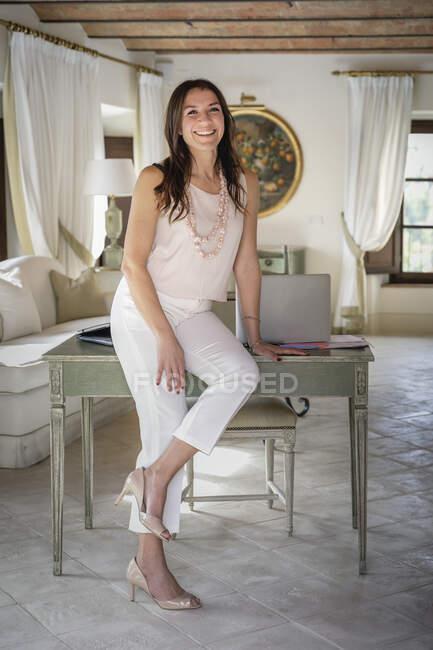 Творча жінка - планувальник весілля спирається на стіл у себе вдома. — стокове фото