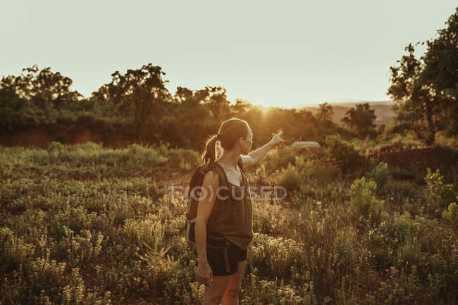 Frau zeigt im Wald auf Sonnenuntergang — Stockfoto