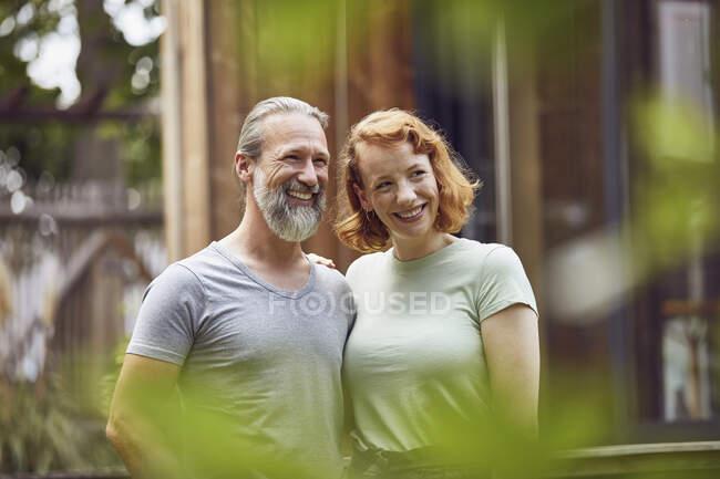 Усміхнена пара, що відвернулася, стоячи навпроти маленького будинку на подвір