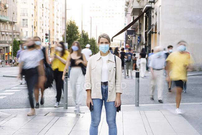 Jovem mulher usando máscara de pé na rua na cidade — Fotografia de Stock