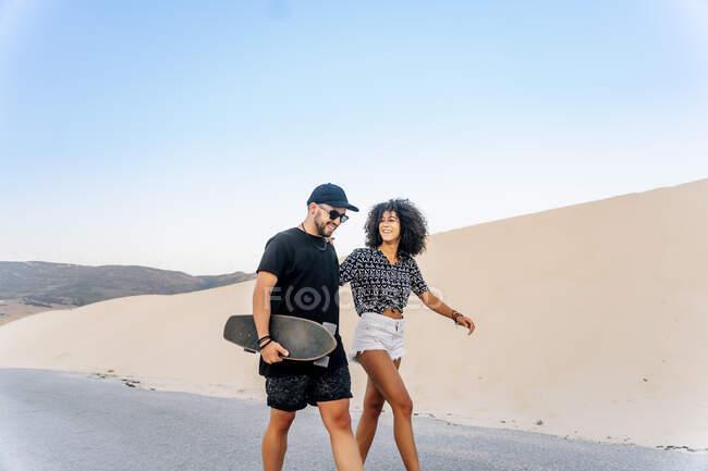 Молода пара йде дорогою піщаною дюною до ясного неба. — стокове фото