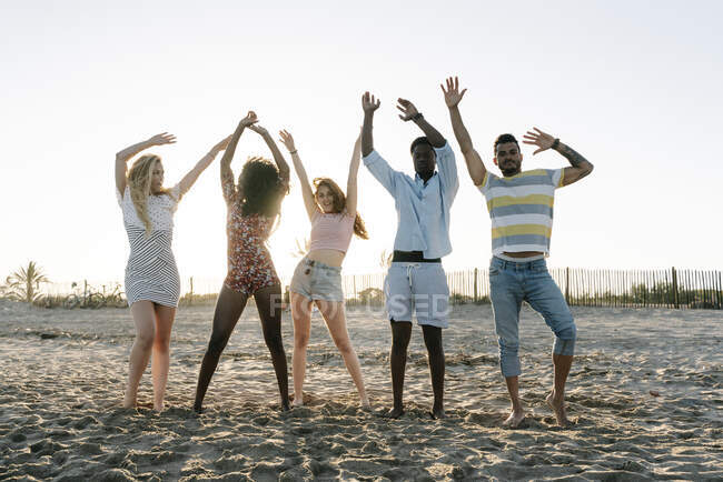 Friends with hand raised standing on beach during sunny day — Stock Photo