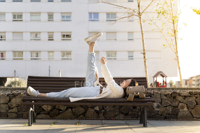Женщина-предприниматель дергает шнурки, пока лежит на скамейке — стоковое фото