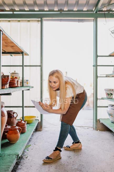Жінка - власник з білявим волоссям на папері під час вивчення кераміки в майстерні. — стокове фото