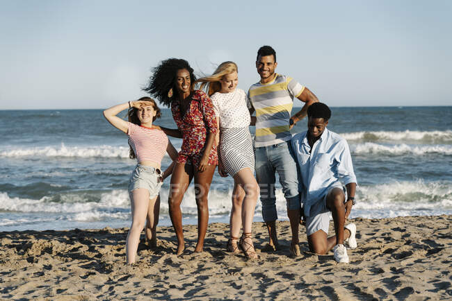 Friends standing on sand against water during sunny day — Stock Photo