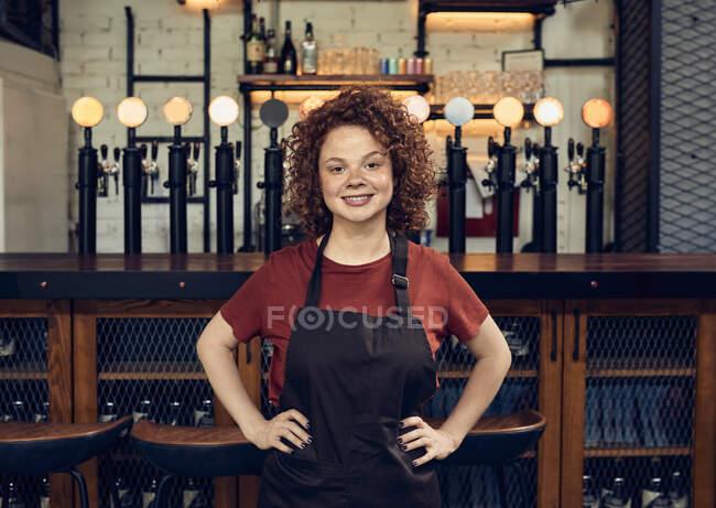 Портрет упевненої офіціантки біля стойки в пабі. — стокове фото