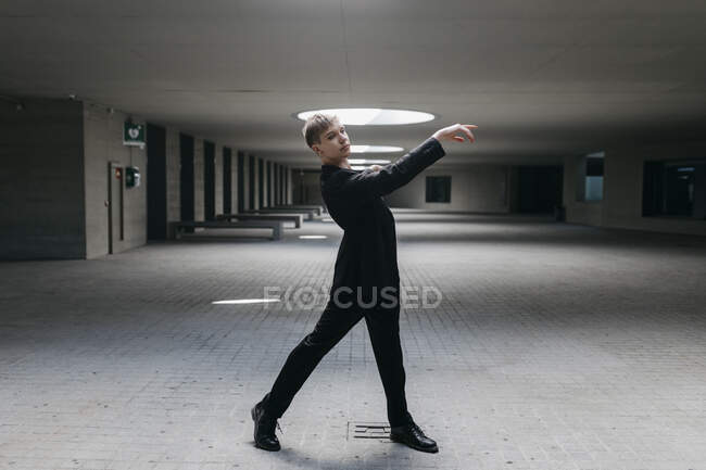 Транс - молодий чоловік у чорному костюмі танцює на підлозі в підвалі. — стокове фото