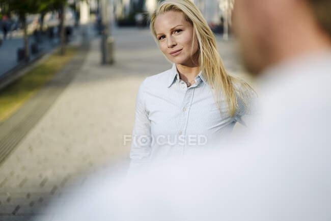 Fiduciosa bella donna professionale in piedi con collega maschio sul marciapiede in città — Foto stock