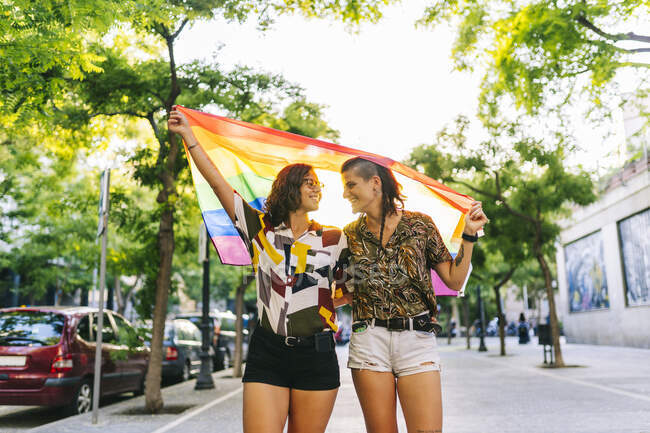 Лесбійська пара дивиться один на одного, тримаючи райдужний прапор на шляху в місті. — стокове фото