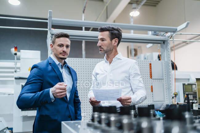 Бизнесмен смотрит на коллегу-мужчину, обсуждая машину на заводе — стоковое фото