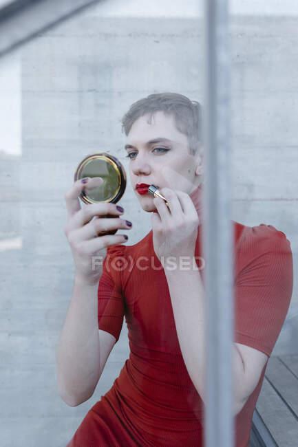 Trans joven aplicación de lápiz labial mientras está sentado en los pasos vistos a través de vidrio - foto de stock