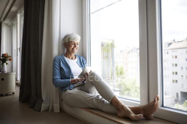 Mulher sênior feliz usando tablet digital enquanto sentado na janela em casa — Fotografia de Stock