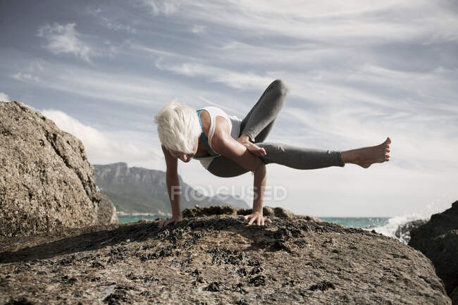 Блондинка практикует аставакрасану на скалах против неба — стоковое фото
